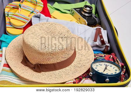 Woven hat, clothes in suitcase. Personal accessories for summer voyage.