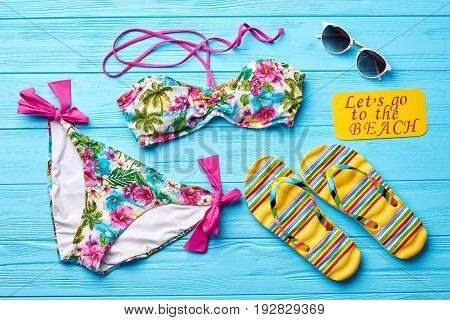 Contemporary woman beach accessories. Swimsuit, glasses, flips, note.
