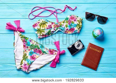 Textile underwear for bathing. Swimsuit, globe, passport, camera, glasses. Concept of vacation abroad.