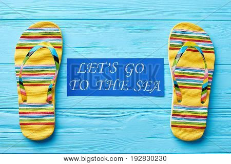 Inscription between two sandals. Footwear and message, wooden painted background. Go to the beach.