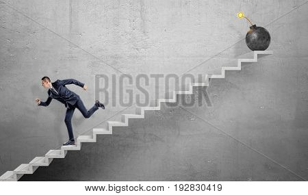 A scared businessman running down grey concrete stairs away from a large iron bomb with a lit fuse. Business trouble. Avoid business pitfalls. Workplace problems.