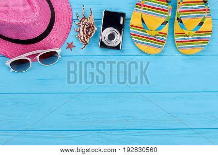 Women vacation stuff on upper border. Hat, glasses, camera, footwear, seashells. Sweet nostalgy about sunny south.