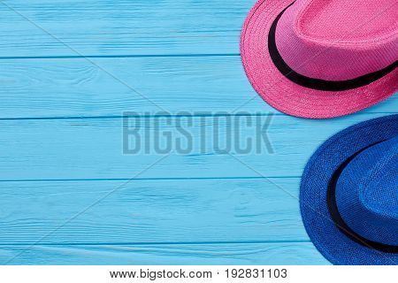 Two colorful summer hats. Woven headgear on blue wooden vintage background.
