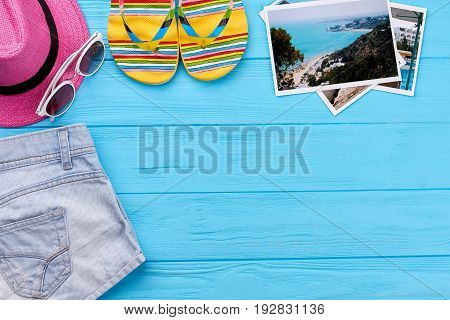 Summer clothing on blue floor. Woman beach items, photos of vacation.