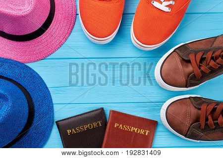 Sport shoes, hats, passports. Accessories for travel abroad on wooden background.