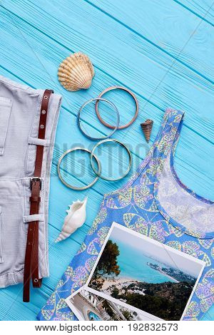 Set of clothes and accessories. Photos of resorts, shorts, shirt, wristlets, seashells. Concept of marine tecreation.