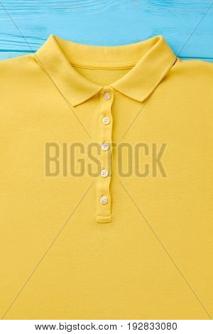 Yellow polo with buttons macro. Trendy clothing for summer vacation.
