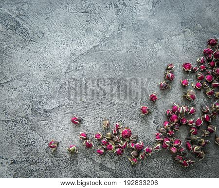 Little buds of dog roses scattered on a dark gray surface, additional copyspace, topview