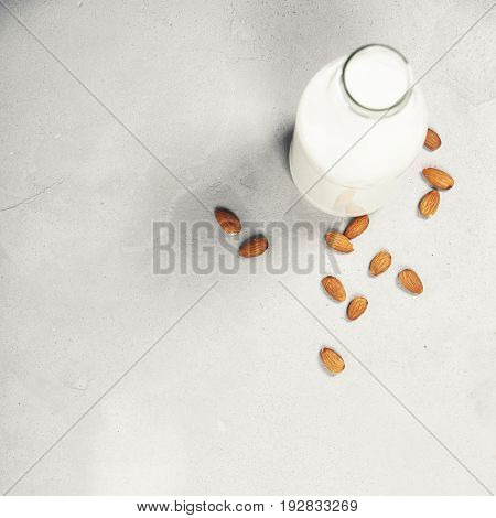 Dairy alternative milk. Almond milk in bottle and fresh nuts over grey background, top view, selective focus, copy space. Clean eating, dairy-free, vegan, detox, allergy-friendly, healthy food concept