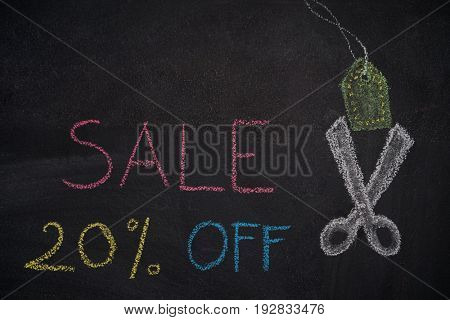 Sale 20% off. Sale and discount price sign with scissors cutting price tag drawn with chalk on blackboard