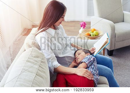 Side view of mother reading a story to her son. Family sitting in the living room
