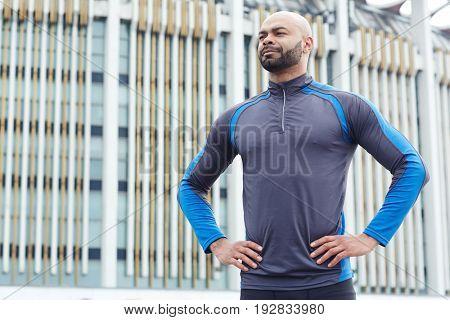 Strong man in sportswear standing in akimbo pose