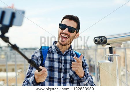 Ecstatic adventurer making selfie while traveling
