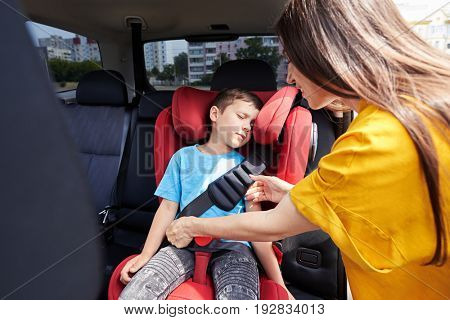 Wide shot of caring mother checking seat belt sleeping son