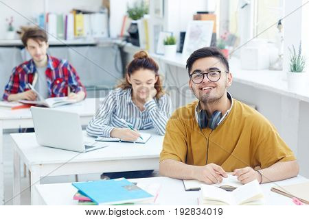 Happy guy with headphones sitting by desk at lesson