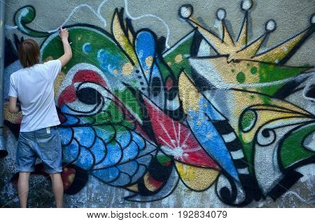 Photo Of A Young Guy In Denim Shorts And A White Shirt. The Guy Draws On The Graffiti Wall A Drawing