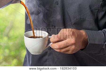 Man pours fresh hot coffee from the coffee pot into the cup