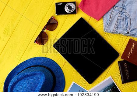 Electronic portable modern device. Background of summer vacation with tablet pc. Stylish accessories for trip abroad.
