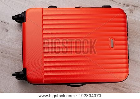 Red traveler suitcase close up. Modern wheeled luggage for travelling abroad.