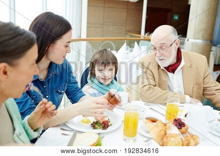 Happy family sitting by table and having breakfast