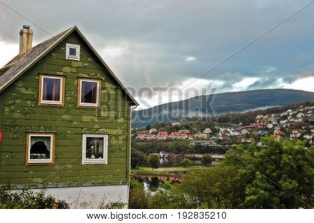 Green Norwegian house by a river and mountain
