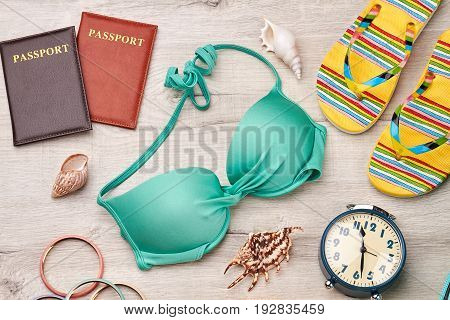 Bright accessories for voyage abroad. Beach items on wooden floor.
