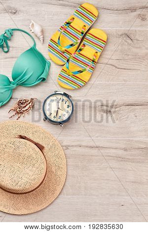 Accessories for marine summer resort. Woven hat, bra, slippers, alarm clock, sea shell, wooden surface. Take pleasure on a beach.
