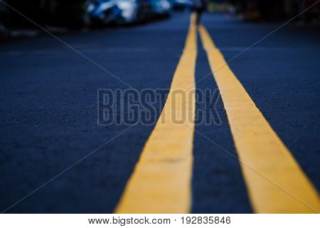 Black street with yellow line selective focus blurred background