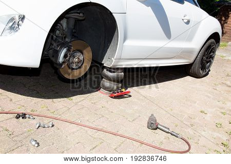 Professional Car Mechanic Changing Car Wheel In Auto Repair Service