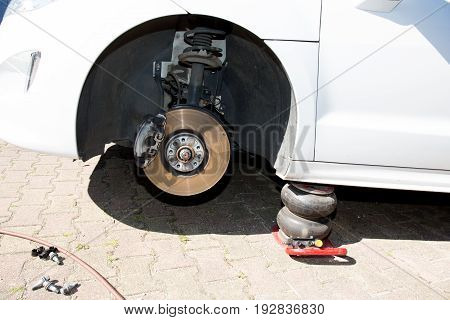 Auto mechanic changing wheel on car outdoor garage