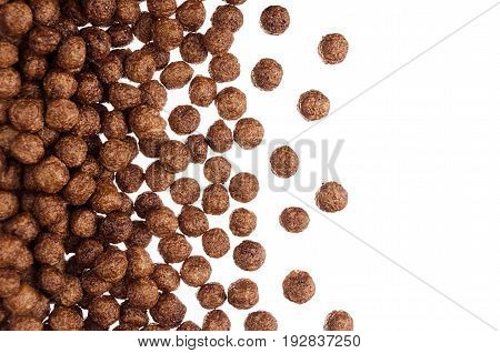Decorative border of chocolate balls corn flakes isolated with copy space background. Cereals texture.