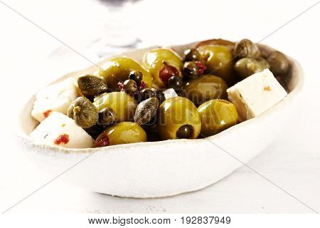 Olives with green peppercorns, capers and feta cheese in a ceramic dish