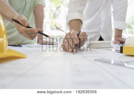 Engineer sketching architectural project on blueprint and laptop