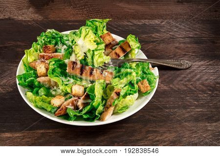 A photo of a plate of chicken Caesar salad with a fork, on a dark rustic background with a place for text