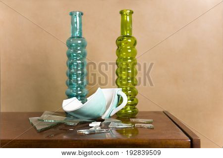 Broken tea cup glass pieces and two vintage glass bottles studio still life.