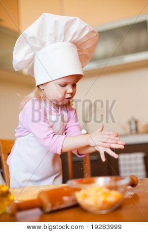 Little baker or cook girl clears hands on kitchen