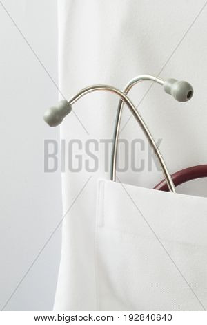 A red stethoscope in the pocket of doctor gown on the white background