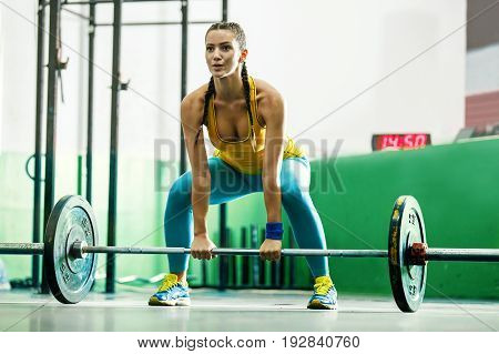 Young strong woman is pulling up weight.