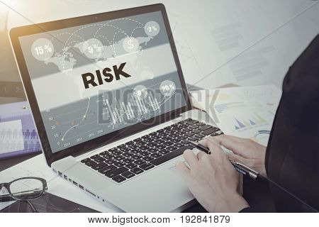 business hand typing on computer keyboard with Risk homepage on the screen financial and banking website web page concept.