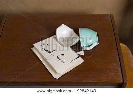 Broken cup on a table and goodbye message concept of family relationships. Studio shot