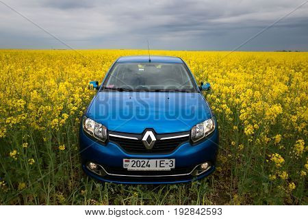 Gomel, Belarus - 24 May 2017: Reno Logan Blue Car Parked On A Rapeseed Field