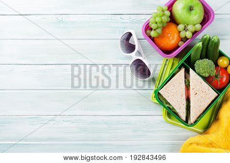 Lunch box with vegetables and sandwich on wooden background. Beach take away food box, towel and glasses. Top view with space for your text