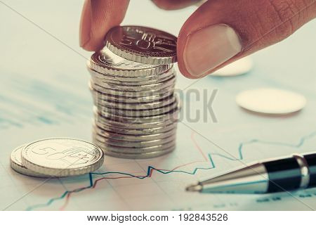 Holding a coin over Singapore coins and financial chart and ballpoint pen