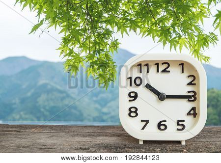 Closeup white clock for decorate show a quarter past ten o'clock or 10:15 a.m. on blurred mountain view background
