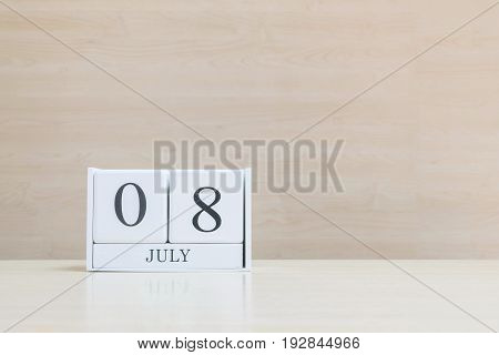 Closeup surface white wooden calendar with black 8 july word on blurred brown wood desk and wood wall textured background with copy space selective focus at the calendar