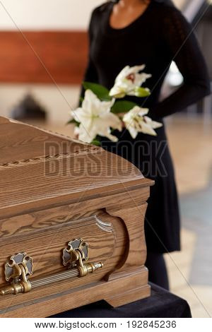 people and mourning concept - woman with flowers and coffin at funeral in church