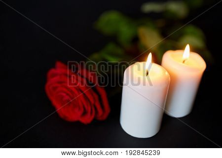 funeral and mourning concept - red rose and burning candles over black background