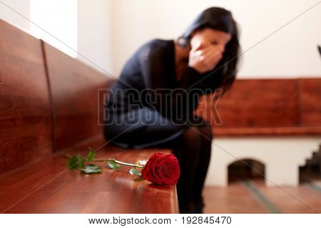 people, grief and mourning concept - crying woman with red rose sitting on bench at funeral in church