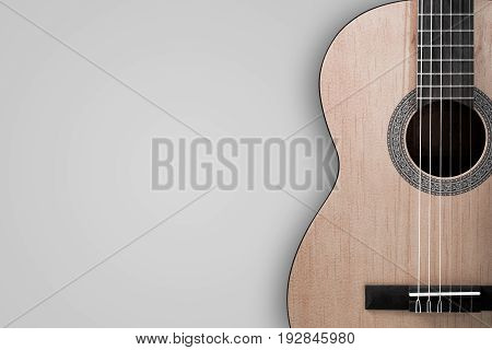 Part of an Acoustic guitar with a shadow on a gray background.