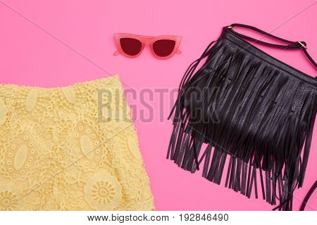 Part Of Yellow Lace Shorts, A Black Bag With Fringe And Rose-colored Glasses. Bright Pink Background